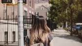 Camera follows girl with backpack walking along sunny New York street, living a casual happy lifestyle slow motion.