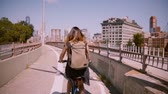 Back view happy girl with flying dark hair riding a bicycle along a separate bike lane in New York City slow motion. Wideo