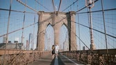 свадьба : Happy romantic couple run forward along Brooklyn Bridge in New York City, hold hands on a beautiful sunny summer day. Стоковые видеозаписи