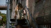 рюкзак : Back view of young woman with backpack and long hair walking up old metal stairs to enter red brick building slow motion