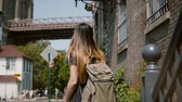 Нью Йорк : Back view of young girl in sunglasses with backpack going down old stairs of red brick building, walking on slow motion.