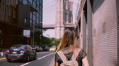 Нью Йорк : Camera follows happy Caucasian girl in fashionable sunglasses with hair blowing in the wind in New York City slow motion Стоковые видеозаписи