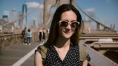 local : Front view of beautiful Caucasian brunette traveler woman in fashionable sunglasses enjoying walk at Brooklyn Bridge 4K.
