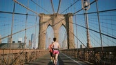 simetria : Two adult women running along Brooklyn Bridge, New York on hot summer day. Diverse age people lead healthy lifestyle 4K.
