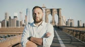 Young positive male Caucasian businessman with arms crossed looking at camera, smiling at Brooklyn Bridge, New York 4K.