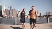 Smiling Caucasian couple walk away from epic New York view near Manhattan skyline holding hands happy slow motion.