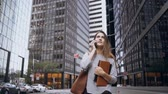megalopolis : Young businesswoman walking through the financial district of New York, America and talking on mobile phone. Slow motion Stock Footage