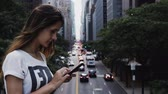 gps : Portrait of young beautiful female standing on the bridge near the traffic road in New York and using the smartphone. Stock Footage
