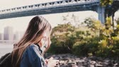 Side view of young traveler girl with backpack walking along calm Brooklyn Bridge river bank with smartphone slow motion