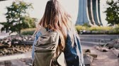 margem do rio : Camera follows young traveler girl with backpack walking along beautiful sunny Brooklyn Park river bank slow motion.