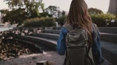 Camera follows beautiful Caucasian female tourist with backpack walking at Brooklyn Park concrete river bank slow motion