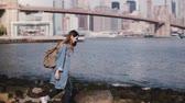 margem do rio : Beautiful Caucasian girl with backpack walking on stone river bank with coffee at amazing New York skyline slow motion