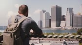 Нью Йорк : Back view of successful businessman standing and enjoying epic Manhattan skyline in sunny summer New York, slow motion.