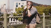 Confident young happy Caucasian entrepreneur talking on the phone with coffee near New York City panorama slow motion.