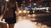 Нью Йорк : Young beautiful woman with shopping bags crossing the traffic road with manhole cover, smoke in New York, America.