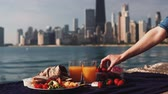 Close-up view of food: fruits and juice on shore of Michigan lake in Chicago, America. Woman puts a strawberry an plate.