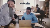 employee : Two young multiethnic colleagues work together in modern loft coworking space, busy office teamwork in the background. Stock Footage