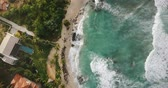 terra : Aerial drone flyover shot of idyllic ocean coastline, foaming white waves reaching exotic tropical resort shore houses.