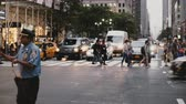 amarelo : NEW YORK AUG 18 2017 - Camera moves sideways along two police officers controlling heavy traffic on a New York street.