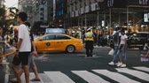 полиция : NEW YORK AUG 18 2017 - Police officer directing traffic flow of cars and people crossing a busy New York City street.