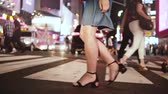 平等 : Atmospheric slow motion shot of young female legs walking across busy crowded street at night in Times Square, New York. 動画素材