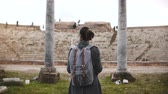 археология : Back view of beautiful young female tourist with backpack and map exploring ancient amphitheater ruins in Ostia, Italy.