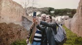 nyugdíj : Excited happy senior man and smiling European young woman taking selfie near old ruins in Ostia, Italy on vacation trip.