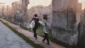 Camera follows two women with a map walking along old antique ruins and streets of Pompeii, Italy on travel vacation. 動画素材