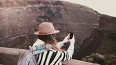 Young happy freelancer girl with backpack taking smartphone photos of Vesuvius volcano crater on vacation in Italy.