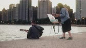 Young creative couple of street artists doing hobby on shore of Michigan, Chicago, USA. Woman draws, man plays guitar. 動画素材