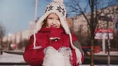 Amazing close-up portrait of fun cute little girl in warm winter clothes throwing snow in the air smiling slow motion. 動画素材