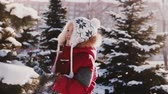 Amazing close-up shot of cute Caucasian little girl in winter clothes having fun beating snow from pine tree slow motion 動画素材