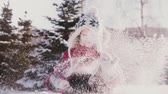 Happy cute little European girl in winter clothes throwing snow in the air, looking at camera and smiling slow motion. 動画素材