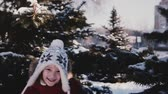 Amazing close-up shot of cute little girl in winter clothes running to camera from behind snowy pine trees slow motion.