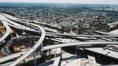 Drone flying left high above big Judge Pregerson freeway junction in Los Angeles with multiple bridges and flyovers. 動画素材