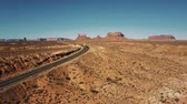 Aerial shot of red cargo truck moving along desert highway road with amazing mountain skyline in Monument Valley, USA.