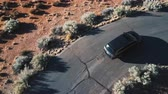 Top view drone follows silver minivan car taking turns on small narrow asphalt desert ring road on a sunny summer day.