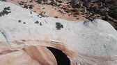 Drone flying over massive white rock formation with big hole, tourist walking over in Arizona mountain desert landscape.