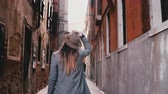 Back view of professional travel blogger girl with camera enjoying exploring ancient narrow streets in Venice, Italy.