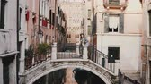 Beautiful perspective view of female tourist with camera walking on bridge over water canal street in Venice, Italy. Stok Video