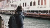 Cinematic back view shot of happy local young woman enjoying atmospheric boat trip along city river in Venice Italy.