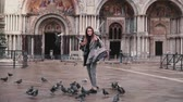 marco : Pigeon sits on arm of beautiful female tourist with smartphone near San Marco cathedral in Venice, Italy slow motion.