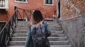 Camera follows beautiful travel blogger woman walking with camera on stairs in Venice street, taking a photo slow motion