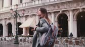 Happy young European businesswoman tourist enjoying walking along beautiful old San Marco city square in Venice, Italy. Stok Video