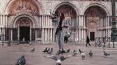 marco : Happy beautiful female tourist with smartphone and pigeons on hand at San Marco square in Venice, Italy slow motion.