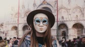 marco : Close-up shot of woman with long hair in traditional carnival mask standing at Venice San Marco square slow motion.