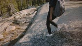雄大な : Camera follows young tourist girl hiking alone with backpack on amazing white rock at Yosemite park USA slow motion.