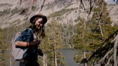 雄大な : Young beautiful tourist girl with backpack and camera smiling at camera while hiking at Yosemite park lake slow motion. 動画素材
