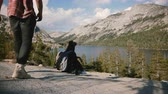 雄大な : Back view tourist girl sits on the edge of big rock, man comes up and sits down by her at Yosemite park lake slow motion