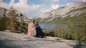 雄大な : Back view happy relaxed tourist romantic couple sit close together enjoying epic view at Yosemite park lake slow motion.
